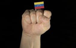 De vuist van de mensenhand met Venezolaanse die vlag op zwarte wordt geïsoleerd Stock Foto