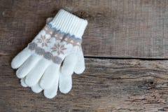 De vuisthandschoenen van de winterkinderen ` s liggen op een houten achtergrond hygge Stock Foto