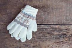 De vuisthandschoenen van de winterkinderen ` s liggen op een houten achtergrond hygge Stock Afbeelding