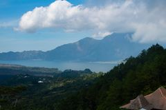 De vulkaan in de wolken op de achtergrond van het Meer Bratan, Atung Bali stock fotografie