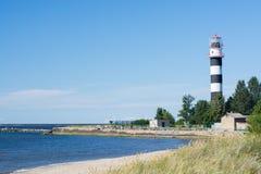 De vuurtoren bevindt zich dichtbij het overzees in de zomer stock foto