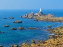 De Vuurtoren van La Corbiere op de rotsachtige kust van het Eiland van Jersey Stock Fotografie