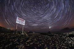 De vuurtoren van Penmon bij nacht met sterslepen stock afbeeldingen