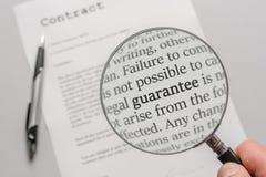De waarborgvoorwaarden van een contract worden gecontroleerd zorgvuldig met een engelstalig vergrootglas - stock afbeeldingen