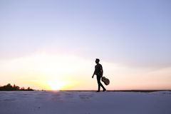 De waardige Arabische kerel loopt met gitaar in handen op zandige heuvel in des royalty-vrije stock fotografie