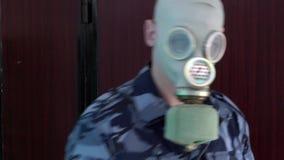 De wacht, gekleed in militaire eenvormig in het masker gaat niet de man met de camera over en breekt dan de camera stock videobeelden