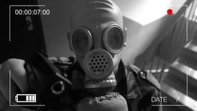 De wacht kleedde zich in militaire die eenvormig in een gasmasker met een kanon bij de toezichtcamera wordt bedreigd stock video
