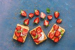 De wafeltjes met room en de verse aardbeien worden bestrooid met chocolade op een roze-blauwe achtergrond Hoogste mening, exempla Royalty-vrije Stock Afbeelding