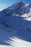 De wandelaar beklimt omhoog door de heuvel in de winterbergen Royalty-vrije Stock Foto's