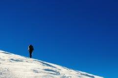 De wandelaar beklimt tot de bovenkant van de berg Stock Foto's