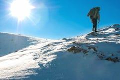 De wandelaar beklimt tot de bovenkant van de berg Stock Afbeeldingen
