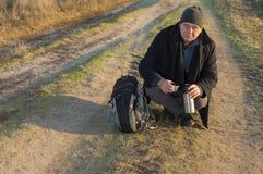 De wandelaar is bereid om één of ander T-stuk te drinken terwijl het zitten op vuile weg bij herfstavond stock foto's