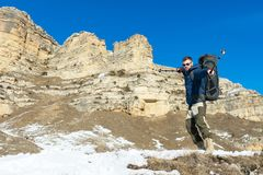 De wandelaar hipster met een grote rugzak bij de voet epische rotsen verklaart bedoeling te winnen Royalty-vrije Stock Fotografie