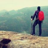 De wandelaar met rode rugzak op scherpe zandsteenrots in rotsimperiums parkeert en lettend op over de nevelige en mistige de lent Stock Afbeeldingen