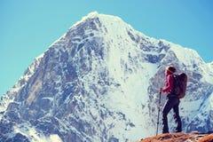 De wandelaar met rugzakken bereikt de top van bergpiek Succes Stock Foto