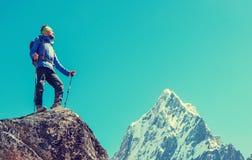 De wandelaar met rugzakken bereikt de top van bergpiek Succes Royalty-vrije Stock Fotografie