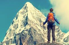 De wandelaar met rugzakken bereikt de top van bergpiek Succes, vrijheid en geluk, voltooiing in bergen Actieve sport royalty-vrije stock afbeeldingen