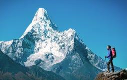 De wandelaar met rugzakken bereikt de top van bergpiek Succes, vrijheid en geluk, voltooiing in bergen Actieve sport royalty-vrije stock foto's