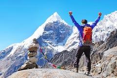 De wandelaar met rugzakken bereikt de top van bergpiek Succes, vrijheid en geluk, voltooiing in bergen Actieve sport royalty-vrije stock foto
