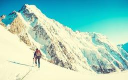 De wandelaar met rugzakken bereikt de top van bergpiek Succesvrijheid en gelukvoltooiing in bergen De actieve sport bedriegt stock afbeelding