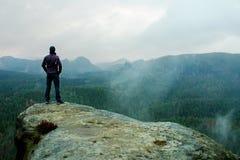 De wandelaar op scherpe klip van zandsteenrots in rotsimperiums parkeert en lettend op over nevelige en mistige de lentevallei Royalty-vrije Stock Foto