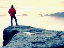 De wandelaar in rood jasje geniet van mening over wolken Berg rotsachtige piek royalty-vrije stock foto's