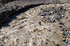 De wandelaar waadt een zeer ruwe bergrivier stock afbeelding