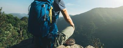 de wandelaar zit op de bovenkant van de zonsopgangberg Royalty-vrije Stock Fotografie