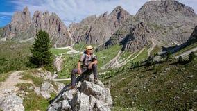 De wandelaar zit op een grote rots Onderzoekt de afstand stock afbeelding