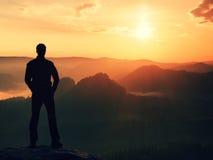 De wandelaar in zwarte tribune op de piek in rotsimperiums parkeert en lettend op over de nevelige en mistige ochtendvallei aan Z stock afbeelding