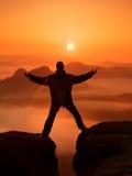 De wandelaar in zwarte viert triomf tussen twee rotsachtige pieken Prachtige dageraad in rotsachtige bergen, zware oranje mist in Royalty-vrije Stock Afbeeldingen
