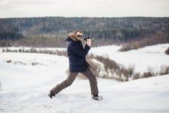 De wandelaarfotograaf geniet van een fijn de winter bospanorama bij zonnige dag Stock Foto