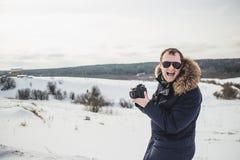 De wandelaarfotograaf geniet van een fijn de winter bospanorama bij zonnige dag Stock Fotografie
