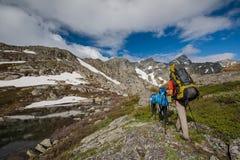 De wandelaars beklimmen rotsachtige helling van berg Stock Fotografie