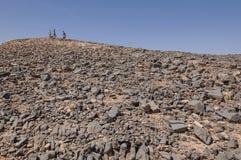 De wandelaars bovenop de Zaagmolenheuvel in Ramon krateen vormen in Stock Foto