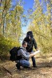 De wandelaars die de manier langs een weg bestuderen nestelden zich in het bos Stock Afbeelding