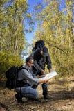 De wandelaars die de manier langs een weg bestuderen nestelden zich in het bos Royalty-vrije Stock Foto