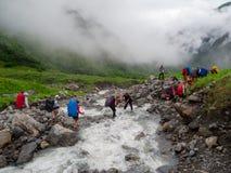 De wandelaars groeperen kruis de bergrivier Stock Afbeeldingen