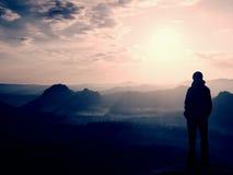 De wandelaartribune op de scherpe hoek van zandsteenrots in rotsimperiums parkeert en lettend op over de nevelige en mistige ocht Stock Foto