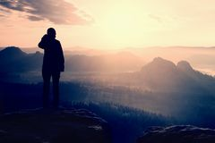 De wandelaartribune op de scherpe hoek van zandsteenrots in rotsimperiums parkeert en lettend op over de nevelige en mistige ocht Royalty-vrije Stock Afbeeldingen