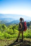 De wandelaarvrouw kijkt verrekijkers op de berg, Stock Foto's