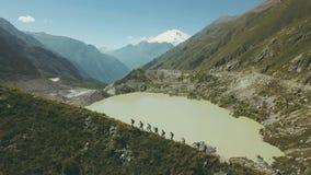 De wandelende mensen die op berg lopen slepen met mening van meer en sneeuwpieken stock videobeelden