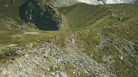 De wandelende mensen die van de hommelmening een berg reizen Toeristengroep die een berg beklimmen stock videobeelden