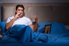 De wanhopige die man in bed is gescheiden stock afbeeldingen