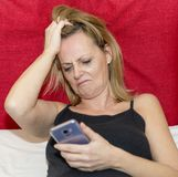 De wanhopige vrouw bekijkt weerzinwekkend het scherm van haar smartphone zettend haar indient haar haar stock fotografie
