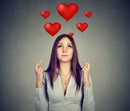 De wanhopige vrouw in liefde die een wens maken houdt haar vingers gekruist stock afbeeldingen