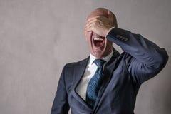 De wanhopige zakenman met dient gezicht in stock fotografie