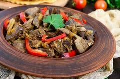 De warme salade van lever en de paprika in een klei werpen op een donkere houten lijst Stock Afbeelding
