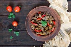 De warme salade van lever en de paprika in een klei werpen op een donkere houten lijst Gebraden lever Stock Afbeelding