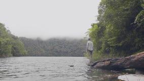 De was van de toeristenmens dient tropische rivier in die onder groene heuvels behandelde wildernis stromen De zitting van de rei stock video